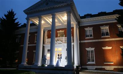 View Photo - Bride and groom standing in front of Bourne Mansion