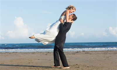 View Photo - Groom holding up bride along ocean shoreline