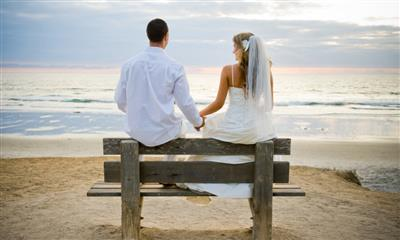 View Photo - Bride and groom holding hands on beach bench