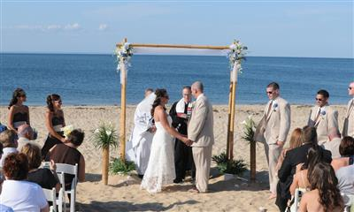 View Photo - Bride and groom beach ceremony