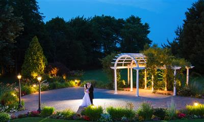 View Photo - Bride and groom kissing by garden