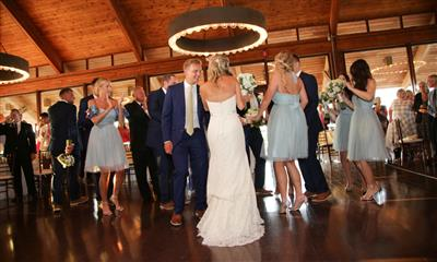 View Photo - Bride and groom with guests inside reception room