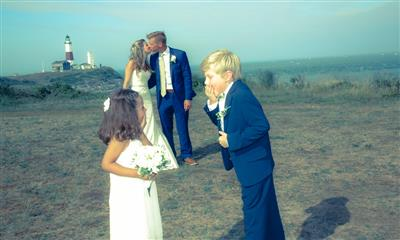 View Photo - Bride and groom kissing with two children sharing giggles