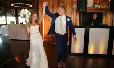 View Photo - Bride and groom walking into reception room holding hands