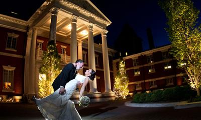 View Photo #18 - Groom holding bride in front of dimly lit Bourne Mansion