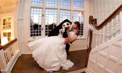 View Photo #3 - Groom leaning his bride for a kiss